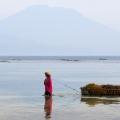 Een vrouw oogst zeewier op Nusa Lembongan, een eilandje voor de kust van Bali. Op de achtergrond de vulkaan Gunung Agung.