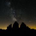Drei Zinnen (Tre Cimi di Lavaredo), icoon van de Dolomieten. Licht vanaf de Po-vlakte zorgt voor een gele gloed, maar verder zijn de sterren en de melkweg zeer helder. Op de Westliche Zinne (rechts) is een lichtje te zien: geen ster, maar een touwgroep in de fameuze noordwand.